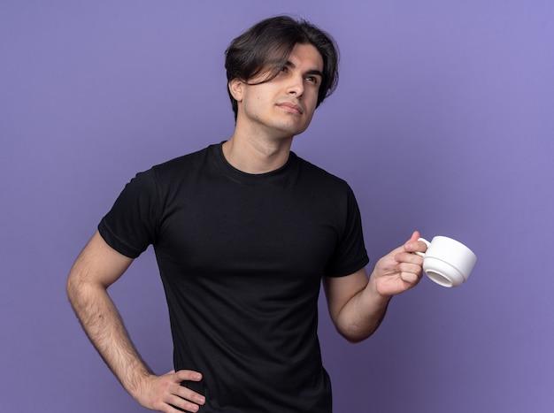Pod wrażeniem młody przystojny facet ubrany w czarną koszulkę, trzymając filiżankę kawy, kładąc rękę na biodrze na białym tle na fioletowej ścianie