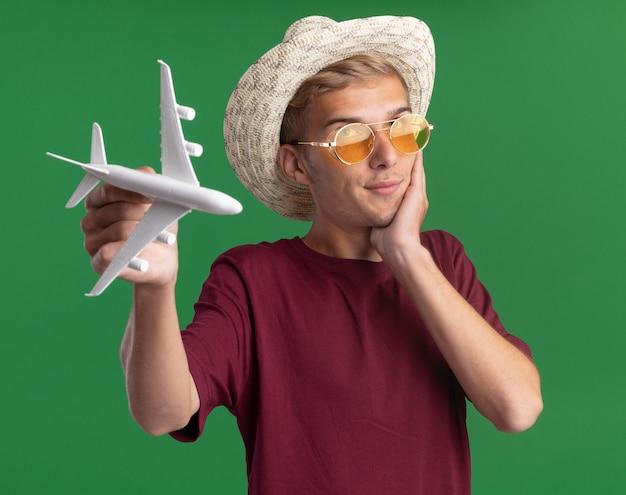 Pod wrażeniem młody przystojny facet ubrany w czerwoną koszulę z okularami i kapeluszem trzymając samolocik kładąc rękę na policzku na białym tle na zielonej ścianie