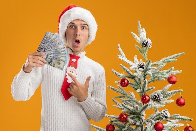 Pod wrażeniem młody przystojny facet w świątecznej czapce i krawacie świętego mikołaja stojący w pobliżu udekorowanej choinki, trzymając i wskazując na pieniądze, patrząc na aparat odizolowany na pomarańczowym tle