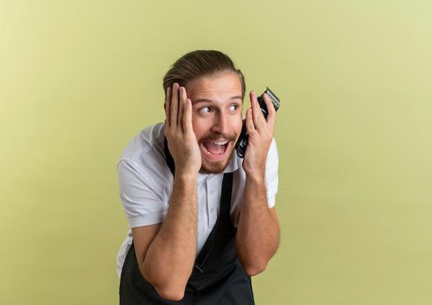 Pod wrażeniem młody przystojny fryzjer trzymając maszynkę do strzyżenia włosów kładąc dłoń na twarzy patrząc na bok na białym tle na oliwkowej zieleni z miejsca na kopię