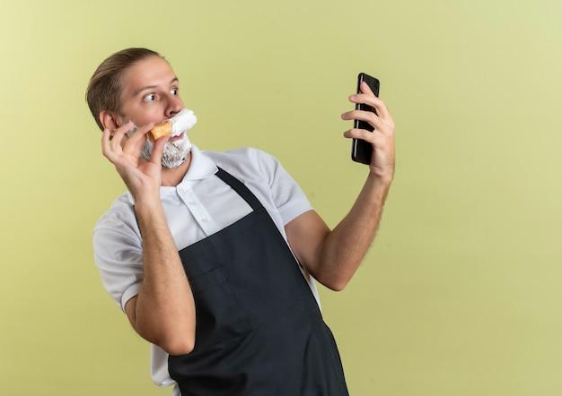 Pod wrażeniem młody przystojny fryzjer w mundurze, trzymając i patrząc na telefon komórkowy oraz nakładając krem do golenia pędzlem do golenia na własną brodę odizolowaną na oliwkowej zieleni z miejscem na kopię