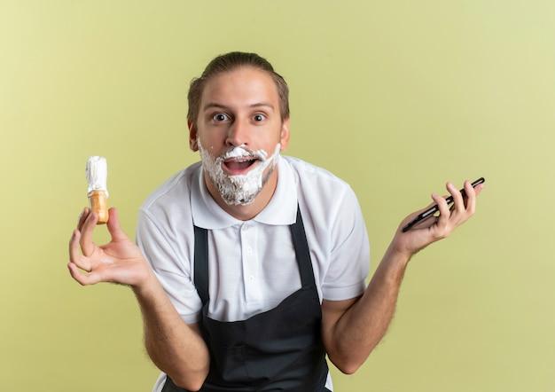 Pod wrażeniem młody przystojny fryzjer w mundurze trzymającym telefon komórkowy i pędzel do golenia z kremem do golenia nałożonym na brodę odizolowany na oliwkowej zieleni