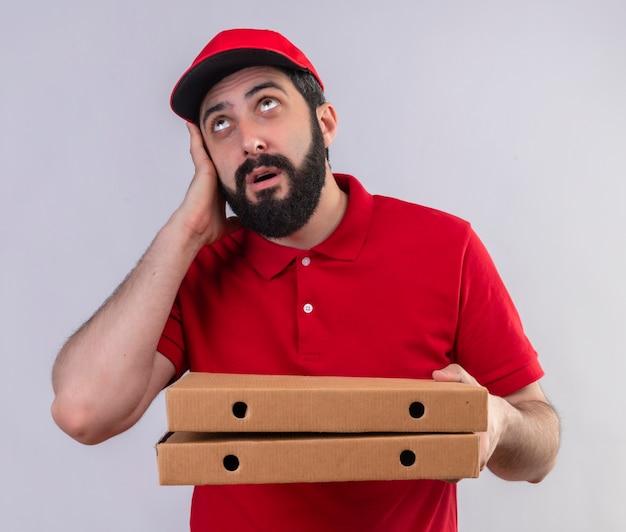 Pod wrażeniem młody przystojny kaukaski mężczyzna dostawy ubrany w czerwony mundur i czapkę, trzymając pudełka po pizzy, kładąc rękę na głowie i patrząc w górę na białym tle