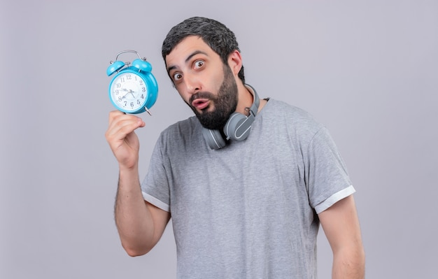 Pod wrażeniem młody przystojny kaukaski mężczyzna nosi słuchawki na szyi i trzyma budzik na białym tle na biały z miejsca na kopię