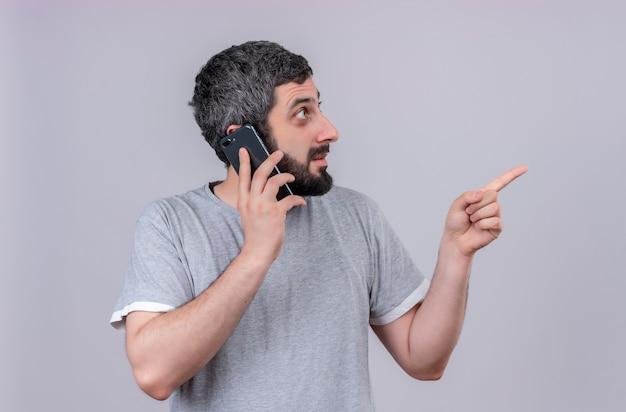 Pod wrażeniem młody przystojny kaukaski mężczyzna rozmawia przez telefon, patrząc i wskazując na bok na białym tle