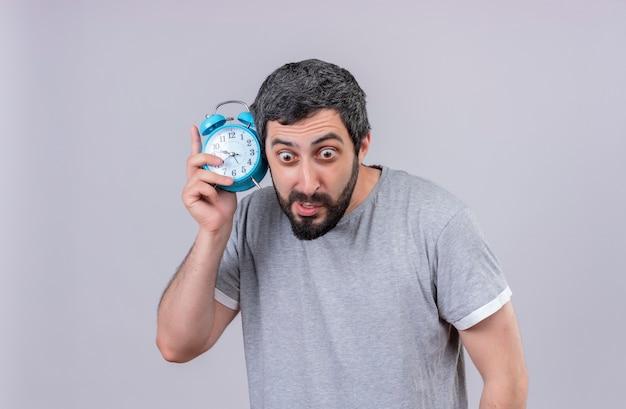 Pod wrażeniem młody przystojny kaukaski mężczyzna trzyma budzik patrząc prosto na białym tle na biały z miejsca na kopię