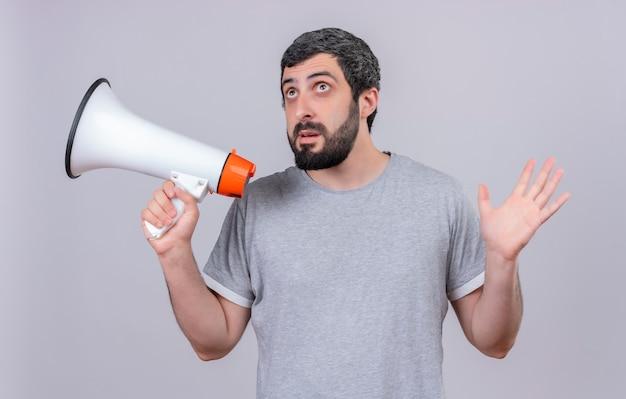 Pod wrażeniem młody przystojny kaukaski mężczyzna trzyma głośnik patrząc w górę i podnosząc rękę na białym tle