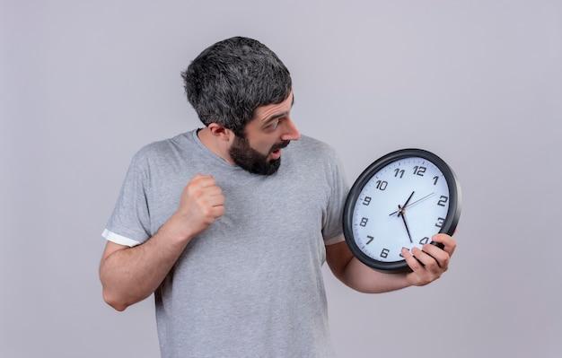 Pod wrażeniem młody przystojny kaukaski mężczyzna trzyma i patrząc na zegar z zaciśniętą pięścią na białym tle