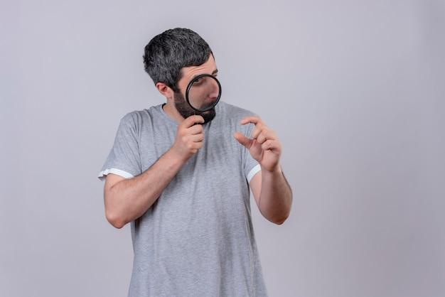 Pod wrażeniem młody przystojny kaukaski mężczyzna trzyma i patrząc przez szkło powiększające z jednym okiem zamkniętym i pokazujący rozmiar na białym tle z miejsca na kopię