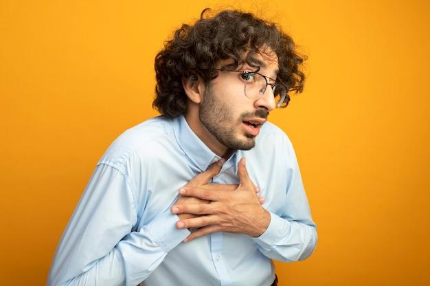 Pod wrażeniem młody przystojny kaukaski mężczyzna w okularach, kładąc ręce na klatce piersiowej na białym tle na pomarańczowej ścianie z miejsca na kopię