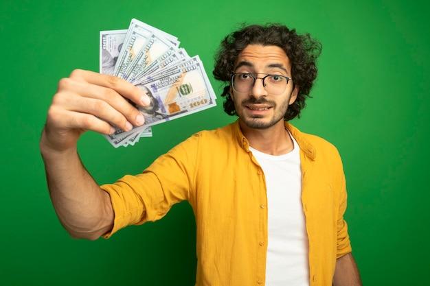 Pod wrażeniem młody przystojny kaukaski mężczyzna w okularach wyciągając pieniądze na białym tle na zielonej ścianie