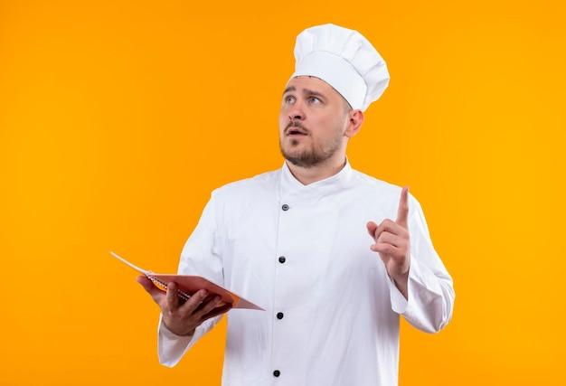 Pod wrażeniem młody przystojny kucharz w mundurze szefa kuchni trzymający notatnik i podnoszący palec patrzący w górę na pomarańczowej ścianie