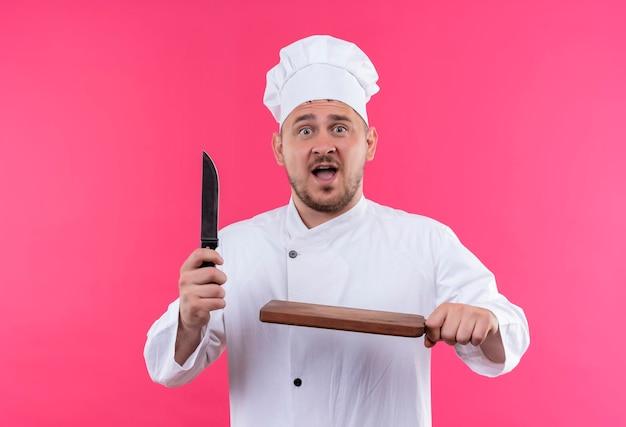 Pod wrażeniem młody przystojny kucharz w mundurze szefa kuchni trzymający nóż i deskę do krojenia na białym tle na różowej ścianie