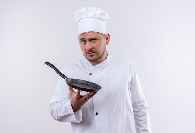 Pod wrażeniem młody przystojny kucharz w mundurze szefa kuchni trzymający patelnię odizolowaną na białej ścianie
