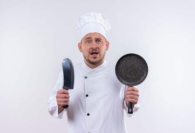 Pod wrażeniem młody przystojny kucharz w mundurze szefa kuchni trzymający tasak i patelnię na izolowanej białej ścianie z miejscem na kopię
