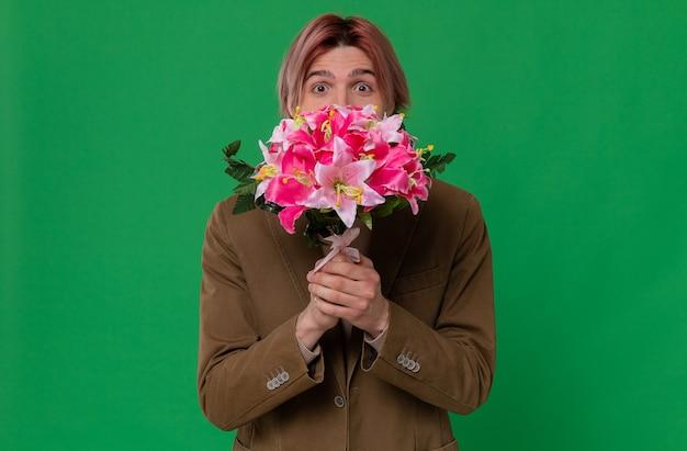 Pod wrażeniem młody przystojny mężczyzna trzyma bukiet kwiatów i patrzy