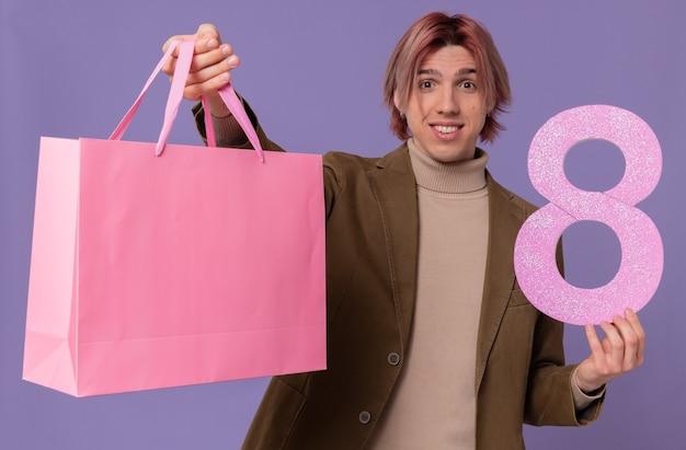 Pod wrażeniem młody przystojny mężczyzna trzyma różową torbę na prezent i numer osiem