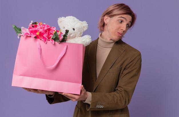 Pod wrażeniem młody przystojny mężczyzna trzyma różową torbę na prezent z kwiatami i misiem patrząc na bok