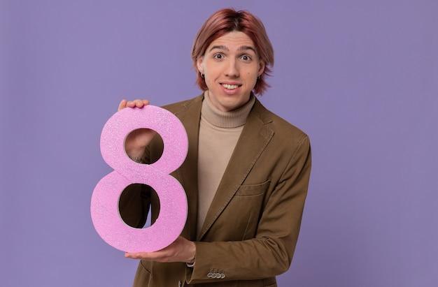 Pod wrażeniem młody przystojny mężczyzna trzyma różowy numer osiem