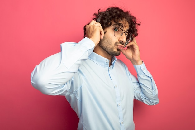 Pod wrażeniem młody przystojny mężczyzna w okularach i słuchawkach, patrząc na przód dotykając słuchawki robi gest pocałunku na białym tle na różowej ścianie