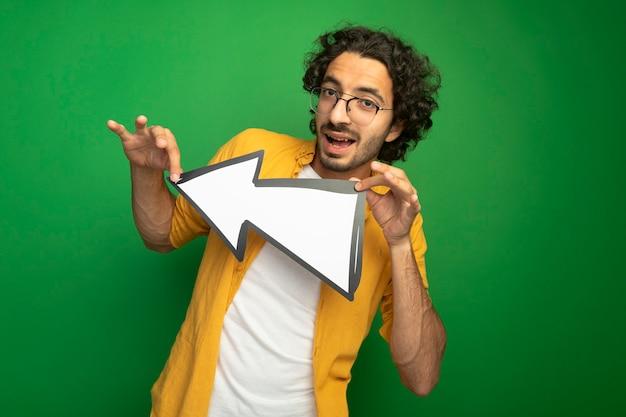 Pod wrażeniem młody przystojny mężczyzna w okularach trzyma znak strzałki, który wskazuje na bok, patrząc z przodu na białym tle na zielonej ścianie