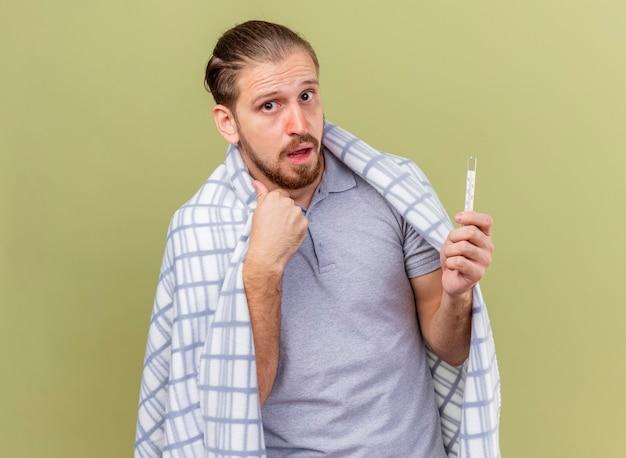 Pod wrażeniem młody przystojny słowiański chory mężczyzna owinięty w kratę, trzymający termometr, trzymając rękę w powietrzu, patrząc na kamerę odizolowaną na oliwkowym tle z miejsca na kopię