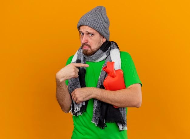 Pod wrażeniem młody przystojny słowiański chory mężczyzna w czapce zimowej i szaliku trzyma i wskazuje na torbę z gorącą wodą odizolowaną na pomarańczowej ścianie z miejscem na kopię