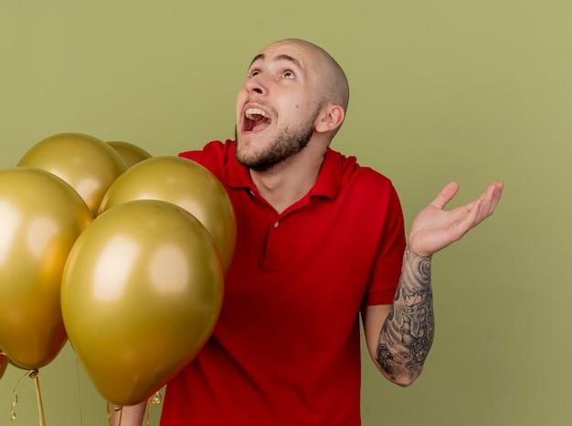 Pod wrażeniem młody przystojny słowiański facet stojący w pobliżu balonów, patrząc w górę pokazując pustą rękę na białym tle na oliwkowym tle