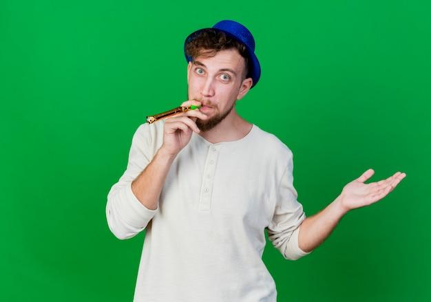 Pod wrażeniem młody przystojny słowiański facet w kapeluszu imprezowym dmuchanie dmuchawy imprezowej patrząc na kamerę pokazującą pustą rękę odizolowaną na zielonym tle z przestrzenią do kopiowania