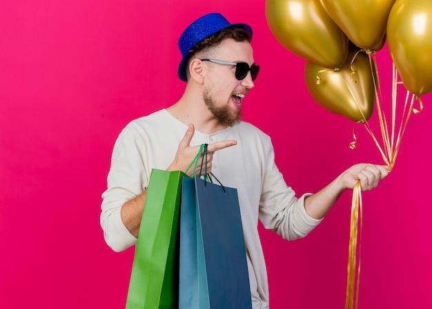 Pod wrażeniem młody przystojny słowiański facet w kapeluszu imprezowym i okularach przeciwsłonecznych, trzymając balony i torby papierowe, patrząc i wskazując na bok odizolowany na różowej ścianie