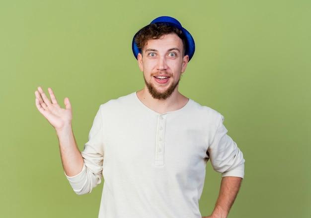 Pod wrażeniem młody przystojny słowiański facet w kapeluszu imprezowym patrząc na kamerę pokazującą pustą dłoń trzymającą drugą w talii odizolowaną na oliwkowozielonym tle z kopią miejsca