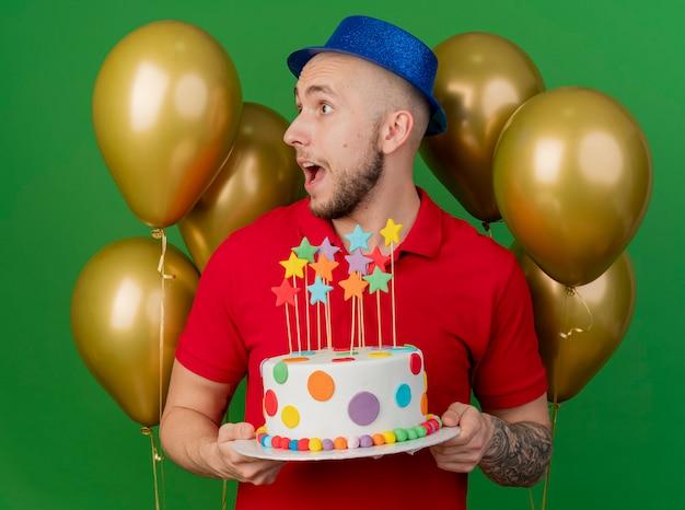 Pod wrażeniem młody przystojny słowiański facet w kapeluszu imprezowym stojący przed balonami, trzymając tort urodzinowy, patrząc z boku na białym tle na zielonym tle