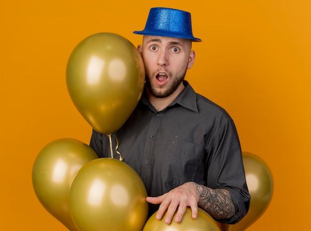 Pod wrażeniem młody przystojny słowiański facet w kapeluszu imprezowym stojący wśród balonów, kładąc rękę na jednym z nich, patrząc na kamerę odizolowaną na pomarańczowym tle