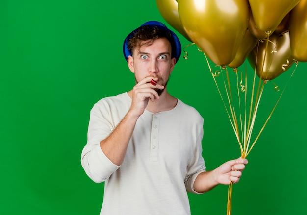 Pod wrażeniem młody przystojny słowiański facet w kapeluszu imprezowym trzymając balony, patrząc na kamerę, wkładając dmuchawę imprezową do ust na białym tle na zielonym tle z miejsca na kopię