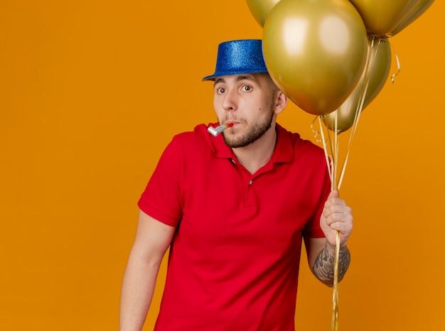 Pod wrażeniem młody przystojny słowiański facet w kapeluszu imprezowym trzymając balony, patrząc na stronę trzymającą dmuchawę w ustach na pomarańczowym tle