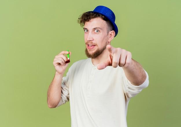 Pod wrażeniem młody przystojny słowiański facet w kapeluszu imprezowym trzymając dmuchawę imprezową patrząc i wskazując na aparat odizolowany na oliwkowym tle z kopią miejsca