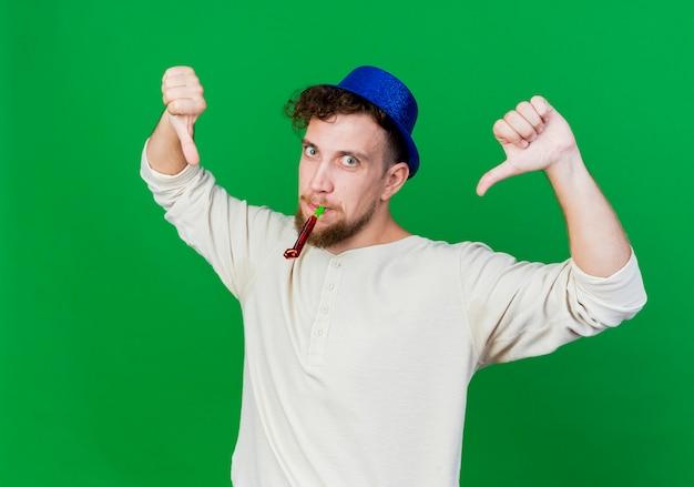 Pod wrażeniem młody przystojny słowiański facet w kapeluszu imprezowym trzymając dmuchawę w ustach patrząc na kamerę pokazując kciuki w dół na białym tle na zielonym tle