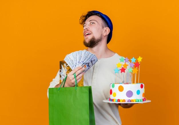 Pod wrażeniem młody przystojny słowiański facet w kapeluszu imprezowym, trzymając pudełko papierowa torba z pieniędzmi i tort urodzinowy z gwiazdami, patrząc na kamery odizolowane na pomarańczowym tle z miejscem na kopię