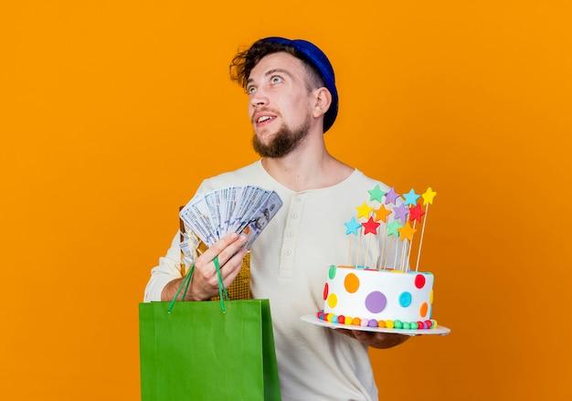 Pod wrażeniem młody przystojny słowiański facet w kapeluszu imprezowym, trzymając pudełko papierowa torba z pieniędzmi i tort urodzinowy z gwiazdami, patrząc w górę na białym tle na pomarańczowym tle z miejscem na kopię