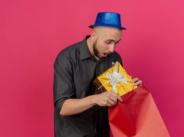 Pod wrażeniem młody przystojny słowiański facet w kapeluszu imprezowym wyciąga paczkę prezentów z papierowej torby patrząc na paczkę prezentów odizolowaną na szkarłatnym tle z miejscem na kopię