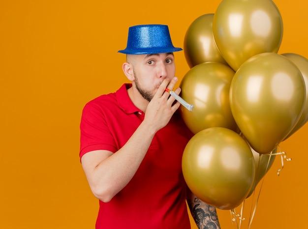 Pod wrażeniem młody przystojny słowiański facet w kapeluszu z balonów, patrząc na kamerę, dmuchanie dmuchawy na białym tle na pomarańczowym tle