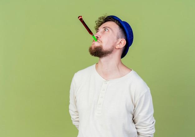 Pod wrażeniem młody przystojny słowiański imprezowicz w kapeluszu imprezowym dmuchanie dmuchawa imprezowa patrząc w górę trzymając ręce za plecami odizolowane na oliwkowym tle z kopią miejsca