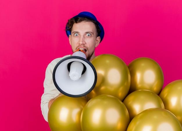 Pod wrażeniem młody przystojny słowiański imprezowicz w kapeluszu imprezowym, patrząc na kamery, rozmawiając przez głośnika na białym tle na szkarłatnym tle z miejsca na kopię