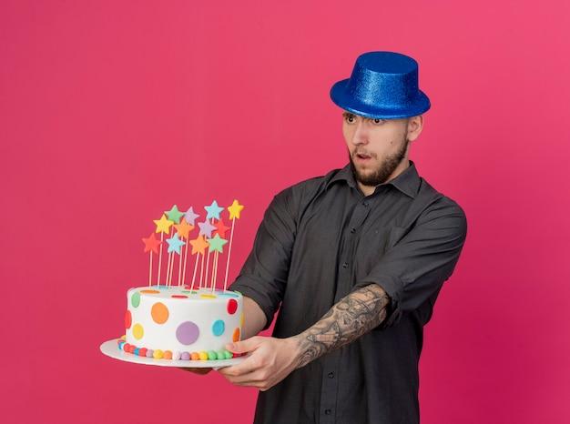 Pod wrażeniem młody przystojny słowiański imprezowicz w kapeluszu imprezowym, rozciągający tort urodzinowy z gwiazdami, patrząc prosto na białym tle na szkarłatnym tle z miejscem na kopię