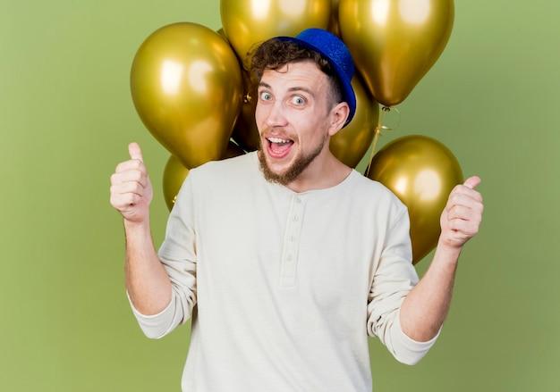 Pod wrażeniem młody przystojny słowiański imprezowicz w kapeluszu imprezowym, stojący przed balonami, patrząc z przodu, pokazując kciuki do góry na tle oliwkowej ściany