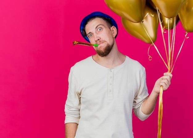 Pod wrażeniem młody przystojny słowiański imprezowicz w kapeluszu imprezowym, trzymając balony i dmuchającą dmuchawę, patrząc z przodu na białym tle na różowej ścianie z miejscem na kopię
