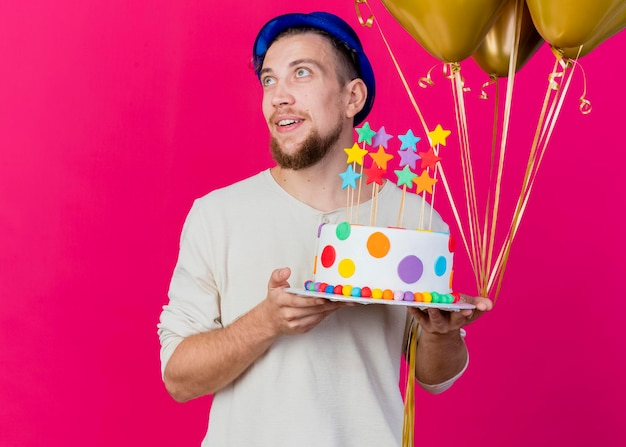 Pod wrażeniem młody przystojny słowiański imprezowicz w kapeluszu imprezowym, trzymając balony i tort urodzinowy z gwiazdami patrząc z boku na białym tle na różowej ścianie z miejscem na kopię