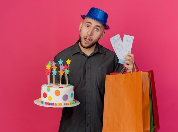 Pod wrażeniem młody przystojny słowiański imprezowicz w kapeluszu imprezowym, trzymając tort urodzinowy bilety lotnicze i papierowe torby patrząc na kamerę na białym tle na szkarłatnym tle z miejsca na kopię