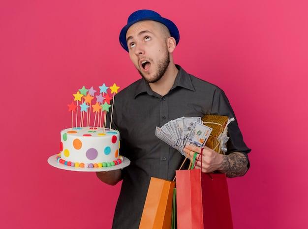 Pod wrażeniem młody przystojny słowiański imprezowicz w kapeluszu imprezowym, trzymając tort urodzinowy pieniądze pakiet prezentów i papierowe torby patrząc w górę na białym tle na szkarłatnym tle