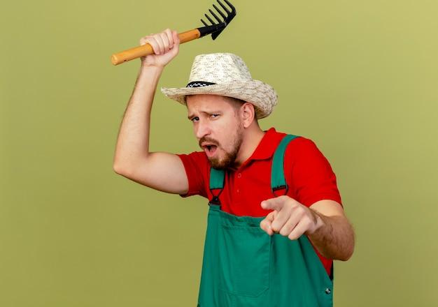 Pod wrażeniem młody przystojny słowiański ogrodnik w mundurze i kapeluszu trzymający prowizję nad głową, patrząc i wskazując na zielono oliwkową ścianę z miejscem na kopię